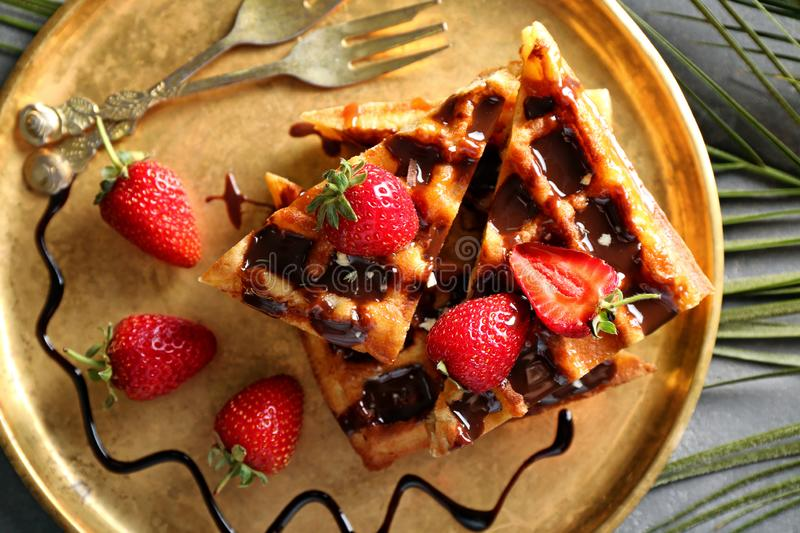 Delicious waffles with strawberries and chocolate sauce on metal tray stock photo