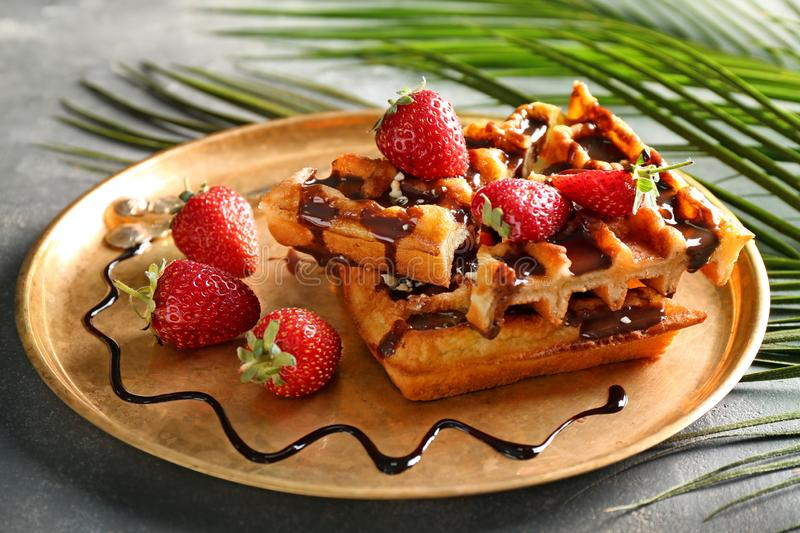 Delicious waffles with strawberries and chocolate sauce on metal tray stock image