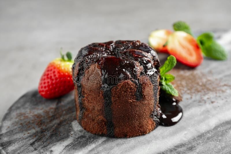 Delicious warm chocolate lava cake on marble board. Closeup royalty free stock images