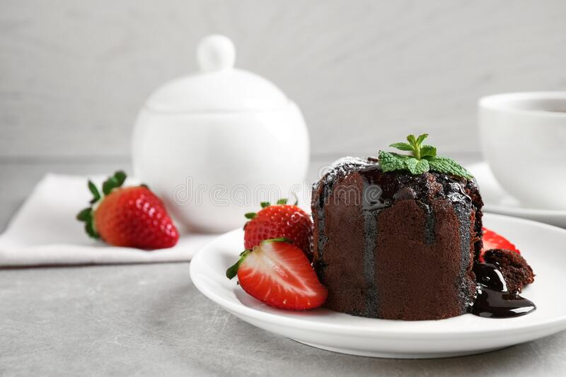 Delicious warm chocolate lava cake with mint and strawberries on table. Space for text stock photo