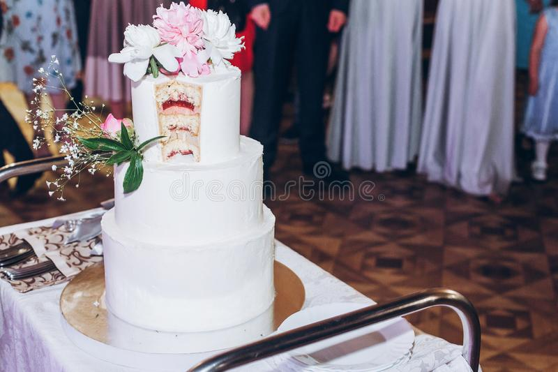 Delicious wedding cake at reception in restaurant with cut slice royalty free stock photography