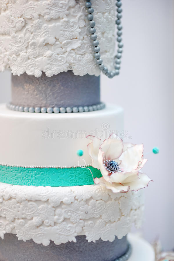 Delicious white and grey wedding or birthday cake. Decorated with flowers royalty free stock images