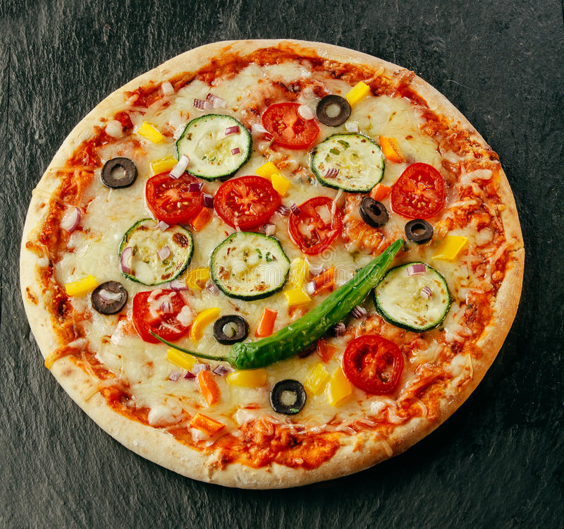 Delicious whole Italian pizza on a dark counter stock image