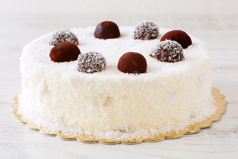 Delicious whole white cake with desiccated coconut powder and cocoa balls icing. On a white rustic wooden table stock images