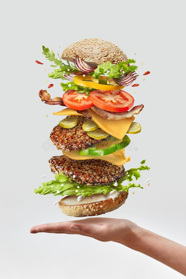 Deliciouse homemade burger on a woman hand with flying fresh ingredients on a white background. Copy space. royalty free stock photos