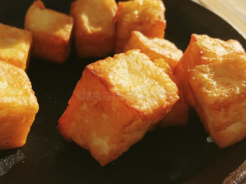 Deliciously fried cheese cubes on a dark plate. royalty free stock photos