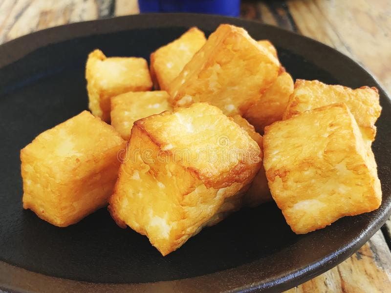 Deliciously fried cheese cubes on a dark plate. royalty free stock photography
