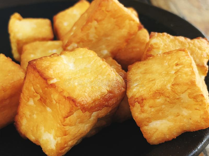 Deliciously fried cheese cubes on a dark plate. royalty free stock image