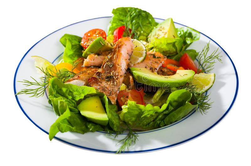 Deliciously salad of  fried  trout with  avocado, greens and tomatoes royalty free stock photography