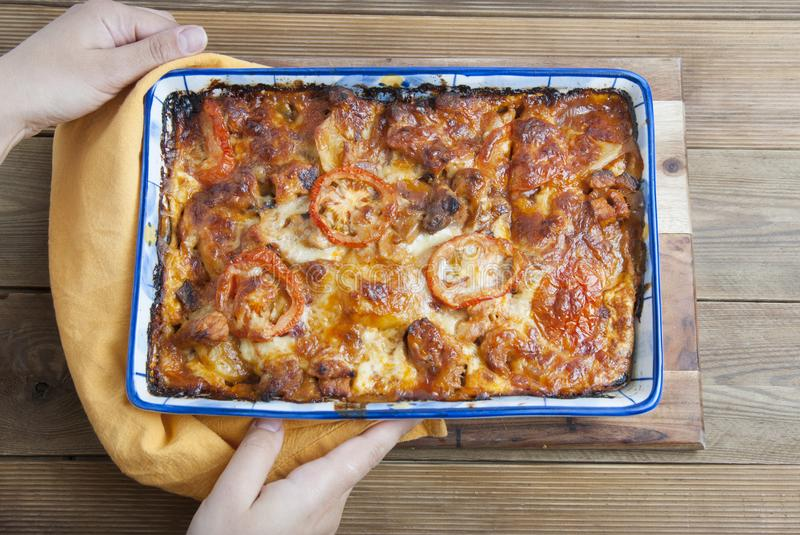 Delicoius homemade Moussaka with potatoes, pork meat, cheese, tomato and deliciouse sauce. Food preparing. Top view. Hands holding royalty free stock photography