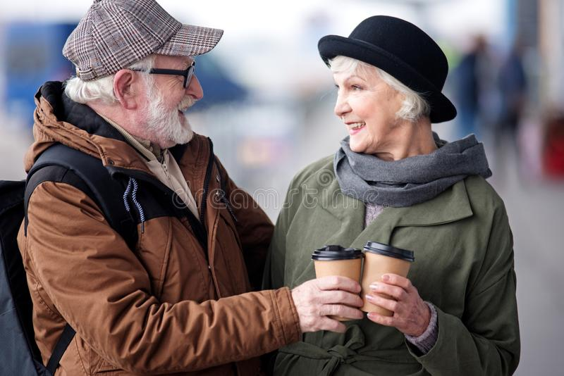 Delighted aged man and woman are drinking espresso on street royalty free stock photography