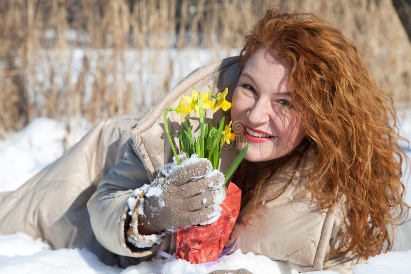 Cheerful red haired woman lying in snow and holding yellow snowdrops royalty free stock photography