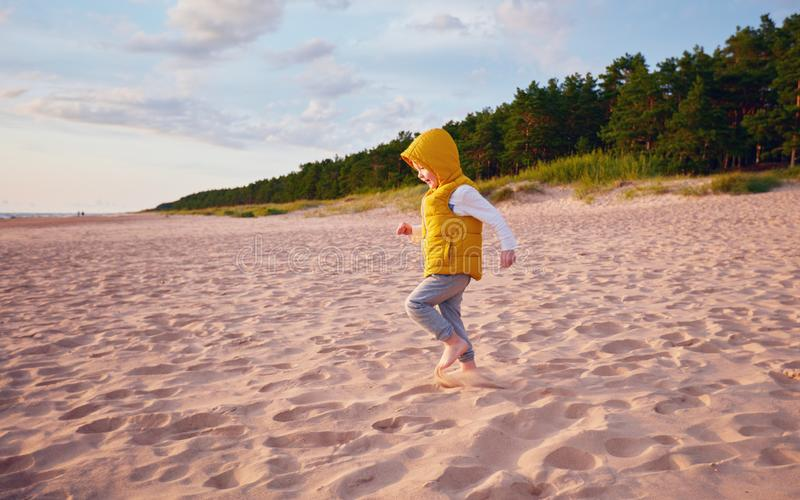 Delighted baby boy having fun, running on the sandy autumn beach near the pine tree forest royalty free stock photo