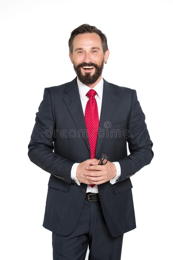 Delighted bearded entrepreneur holding spectacles in hands. Waist up of charismatic bearded entrepreneur expressing happiness while standing in front of camera stock image