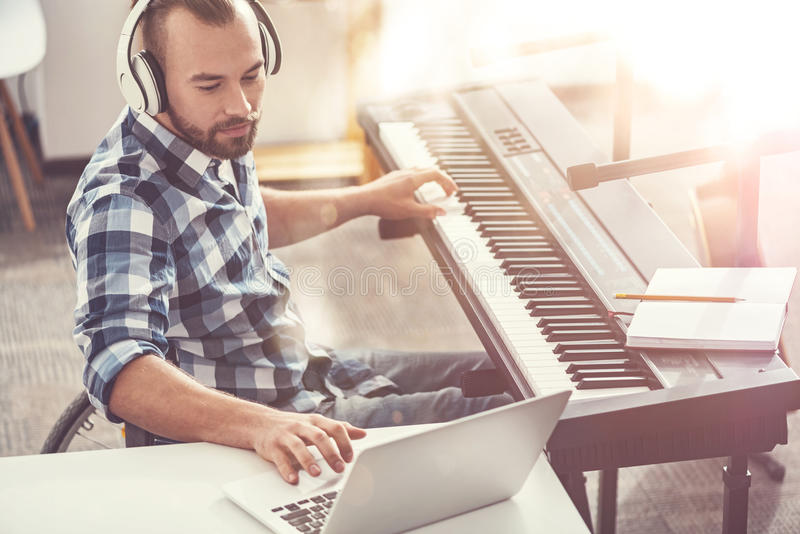 Delighted bearded man making new single stock photo