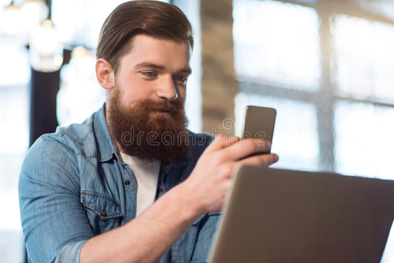 Delighted bearded man sitting at the table. Personal view. Pleasant content handsome bearded man sitting at the table and smiling while holding cell phone royalty free stock photos