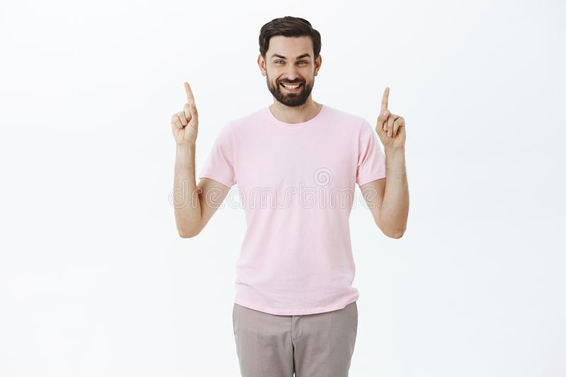 Delighted charismatic happy man with beard and dark hair smiling with broad white grin at camera as showing copy space stock images