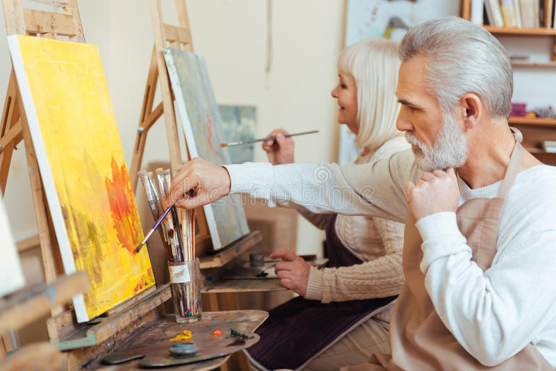 Delighted colleagues drawing in painting class. Sweet cooperation. Delighted talented concentrated colleagues drawing a picture while spending time in painting royalty free stock photo