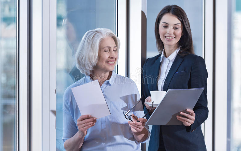 Delighted colleagues laughing during coffee break stock photo