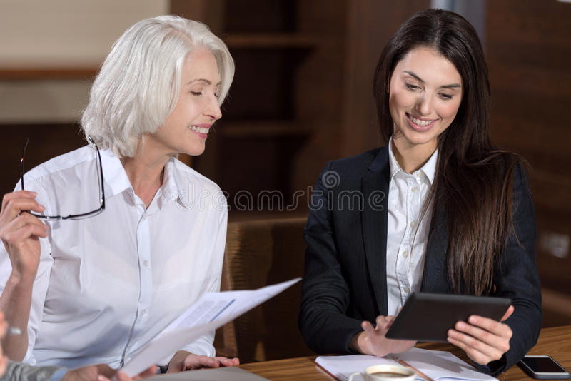 Delighted colleagues sharing results of their work. Common ideas. Delighted female friendly colleagues sharing results of their work while making project and royalty free stock photo