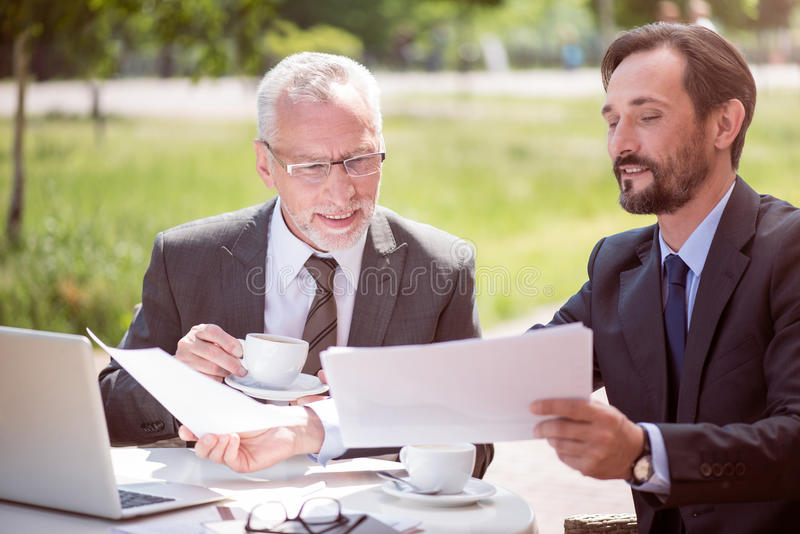 Delighted colleagues sitting at the table. Common project. Pleasant delighted smiling colleagues sitting at the table and working with papers royalty free stock photos