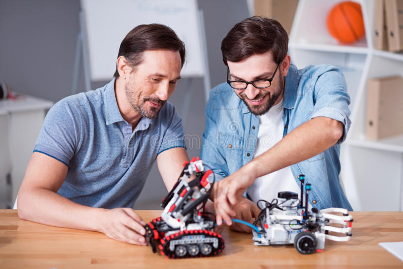 Delighted colleagues testing robot. Happy to work together. Cheerful delighted professional colleagues sitting at the table and testing robot while being royalty free stock photos