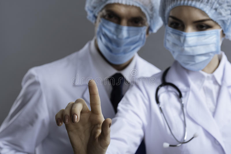 Delighted colleagues using medical glass. Work together. Delighted professional friendly colleagues using medical glass while wearing face masks and surgical stock photography