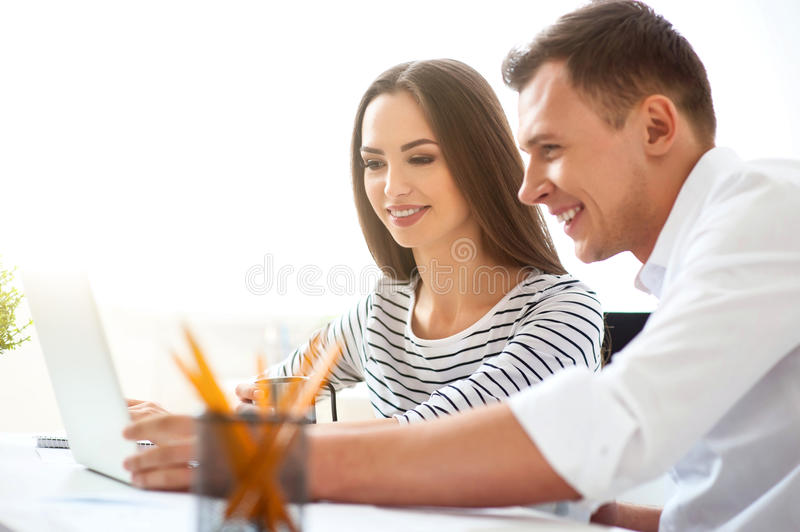 Delighted colleagues working on the laptop. Involved in work. Cheerful delighted smiling colleagues sitting at the table and working on the laptop while stock photo