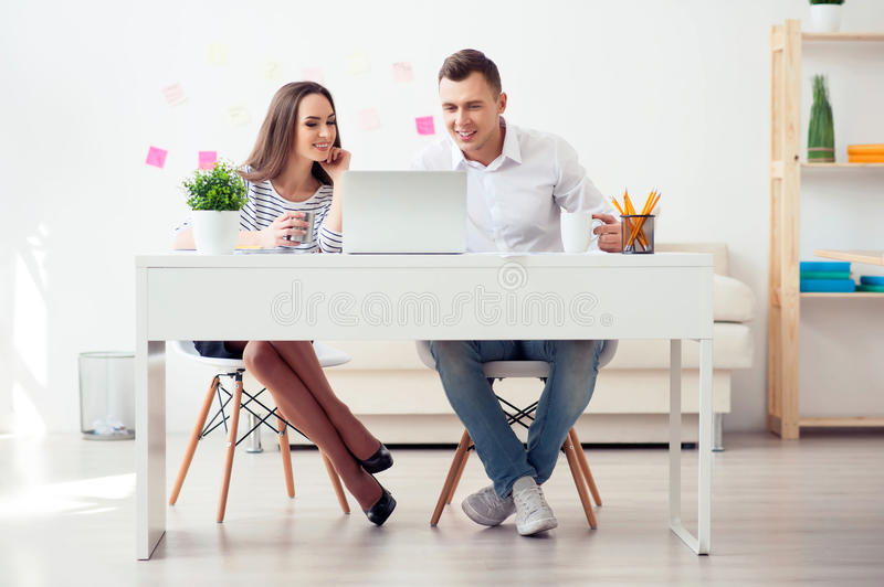 Delighted colleagues working on the laptop. Moment of relaxation. Joyful delighted smiling colleagues sitting at the table and working on the laptop while royalty free stock photos