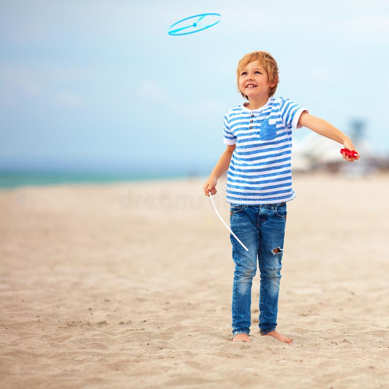 Delighted cute young boy, kid having fun on sandy beach, playing leisure activity games with propeller toy royalty free stock photos