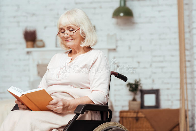 Delighted disabled woman reading book. Time for hobby. Pleasant delighted elderly woman in wheelchair reading book while resting at home royalty free stock photo