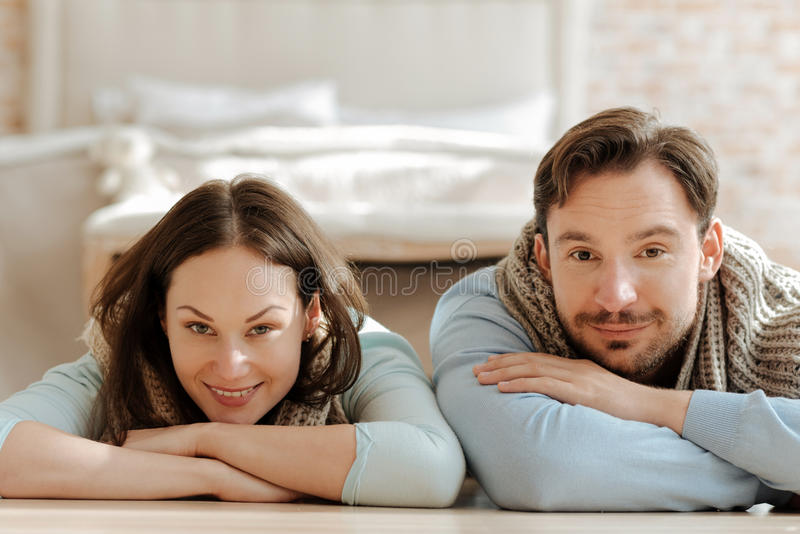 Delighted divertiu os pares que sorriem em casa fotografia de stock