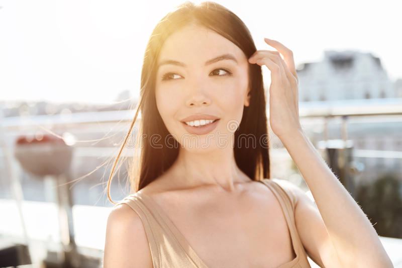 Delighted dreamy woman fixing her hair royalty free stock photo