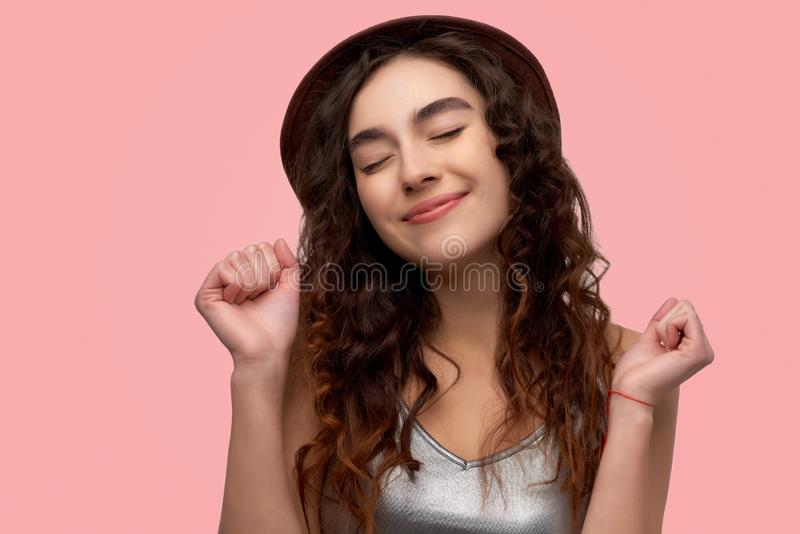 Delighted emotive European woman clenches fists, celebrates triumph, stands over pink background, bursts out from good feelings royalty free stock photography