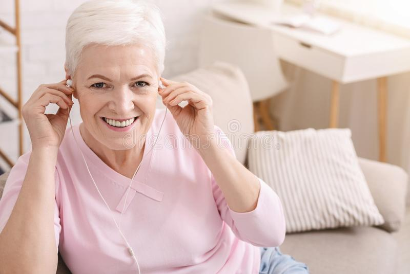 Delighted envelheceu a mulher que escuta a música em casa foto de stock royalty free