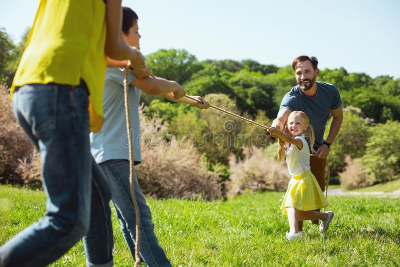 Delighted family playing a game in the park royalty free stock images
