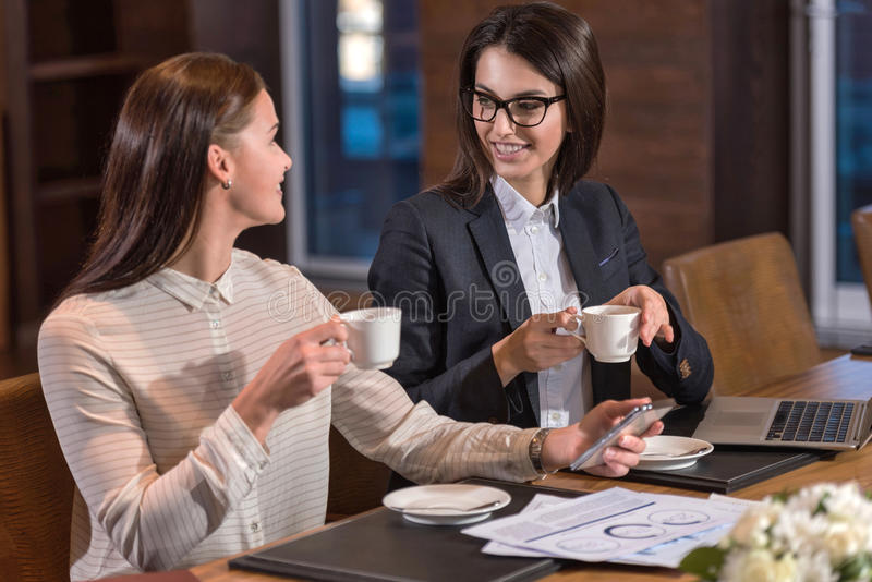Delighted female colleagues drinking tea in an office. Time for break. Delighted young female colleagues drinking tea while working and making project in an royalty free stock image