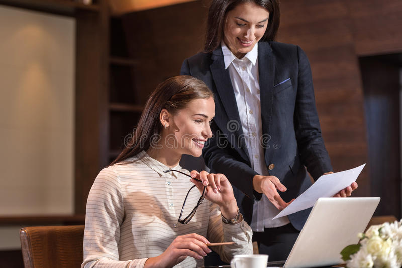 Delighted female colleagues working together in office. Friendly workers. Delighted young female colleagues working together and discussing project while royalty free stock photo