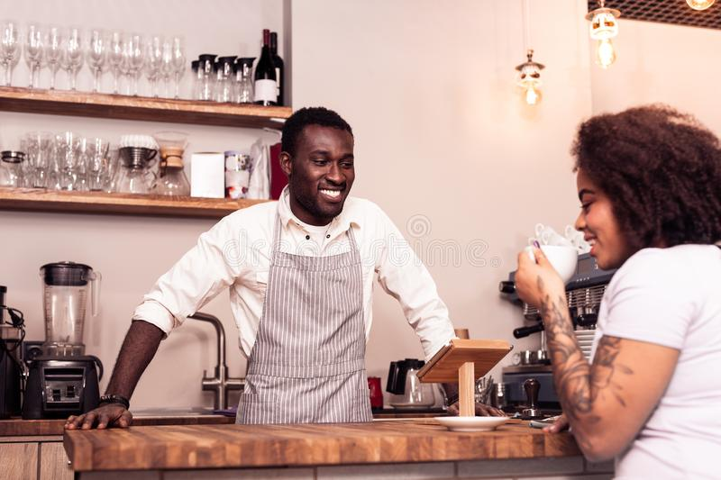Delighted friendly barista smiling to a client. Excellent service. Delighted friendly barista smiling to a client while taking a order for her stock photo