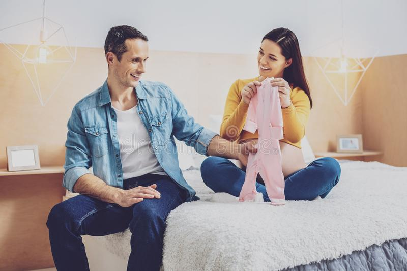 Delighted future daddy staring at little clothe stock photo
