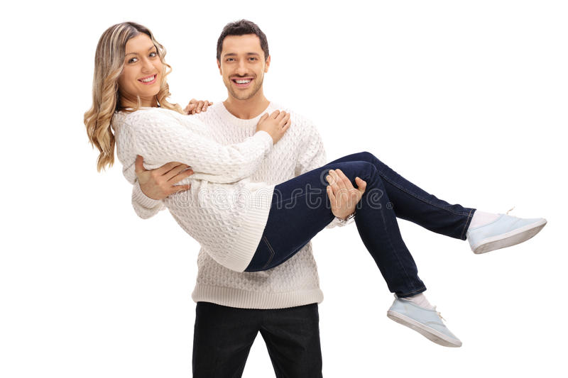 Delighted guy holding a girl in his arms. Isolated on white background stock image