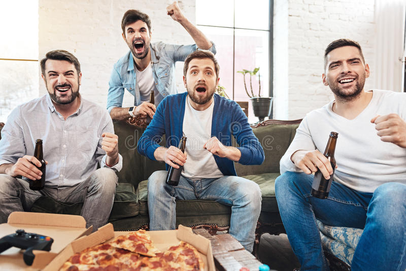 Delighted handsome men being happy for their football team. Football fans. Happy handsome attractive men drinking beer and watching football while supporting royalty free stock photography