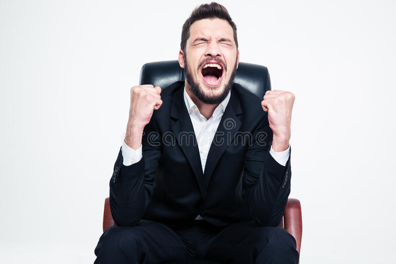 Delighted happy bearded young businessman sitting and celebrating success royalty free stock images