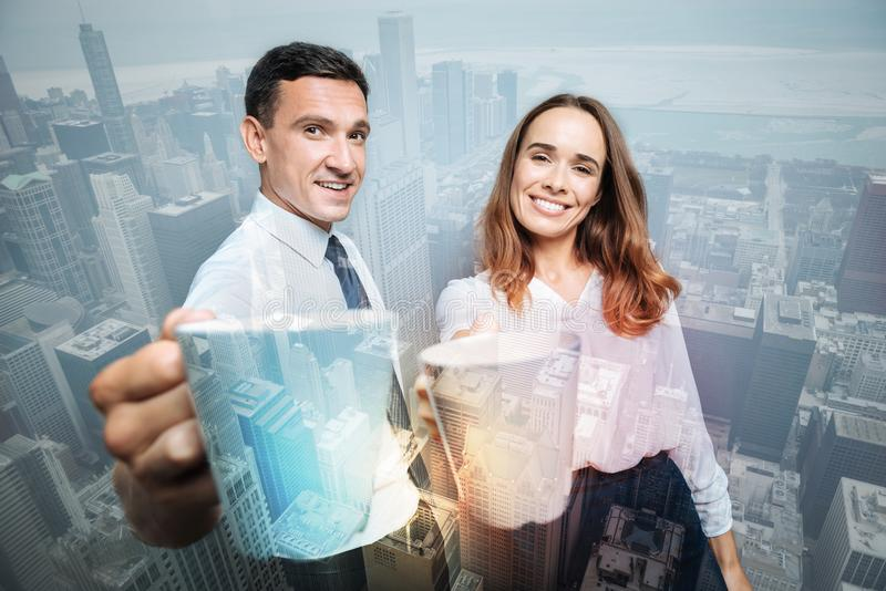 Delighted happy colleagues drinking tea. Pleasant interaction. Delighted nice happy colleagues smiling and having tea together while being in a positive mood royalty free stock image