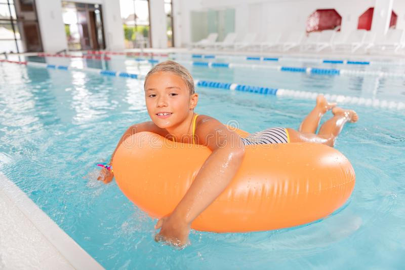 Delighted happy girl enjoying time in the pool stock image