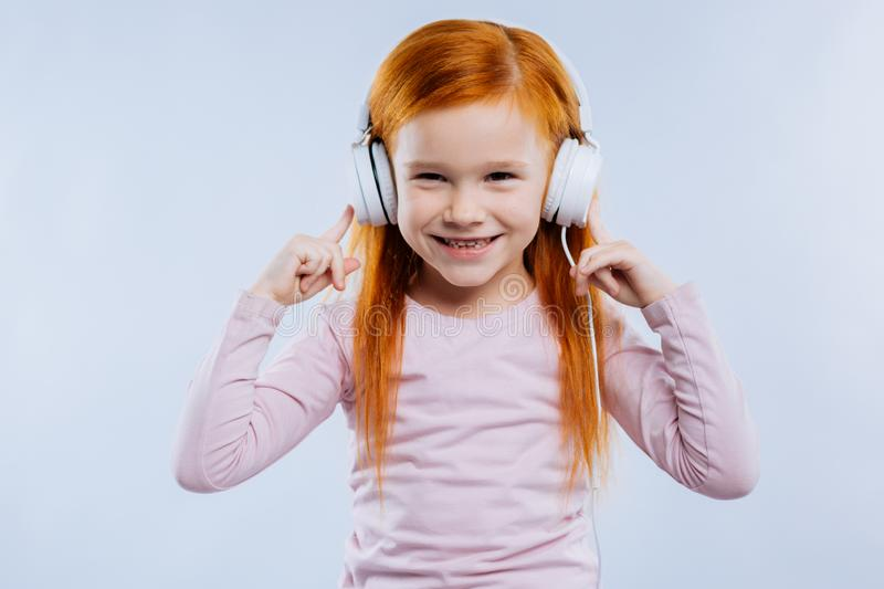 Delighted happy girl pointing at the headphones stock photography