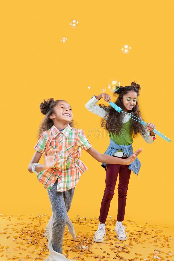 Delighted happy girls playing with soap bubbles stock image