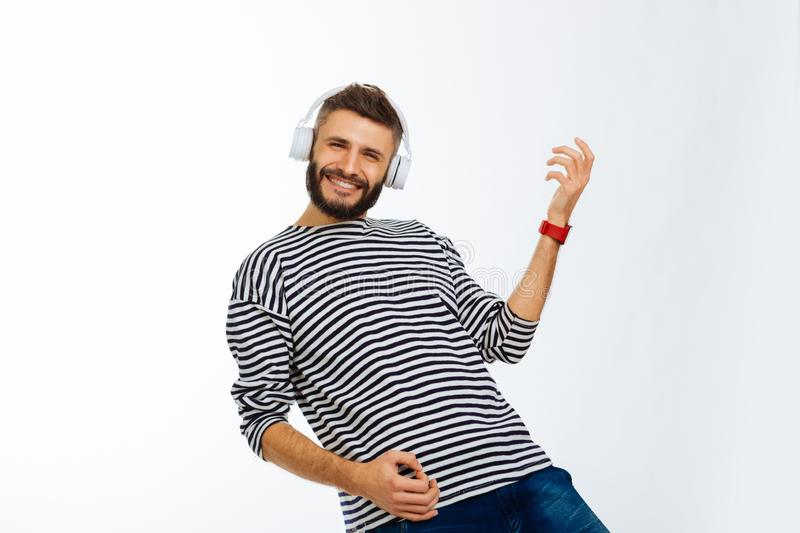 Delighted happy man playing his favourite song royalty free stock images