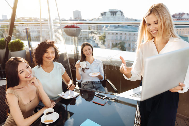 Delighted happy woman holding a laptop. Showing a presentation. Delighted happy positive women holding a laptop and pointing at it while showing a presentation royalty free stock photos