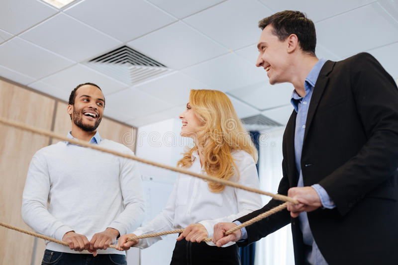 Delighted joyful colleagues enjoying their activity. How to be a team. Delighted joyful positive colleagues standing together and holding the rope while enjoying stock photo